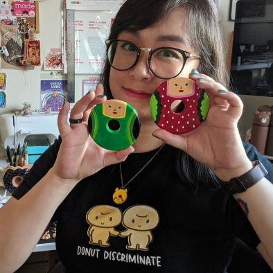 Me, holding up two handmade Katamari-themed clay donuts painted like The Prince and Ichigo